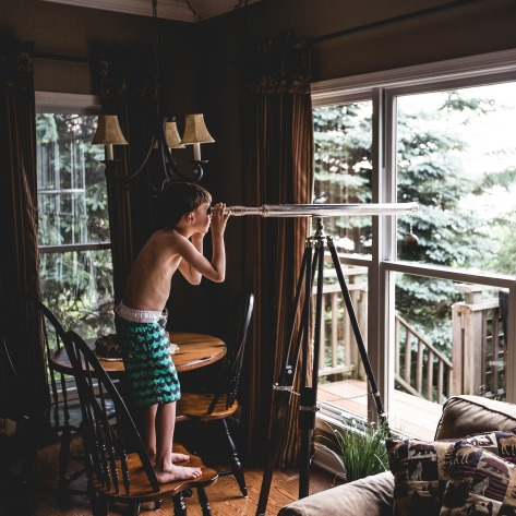 A boy using a long refracting telescope